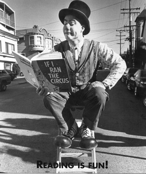 "Bozwick the clown sits in the middle of a San Francisco street on a stepladder reading a book called ""If I ran the circus;"" at the bottom of the photo is the caption ""Reading is Fun!"""