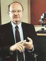Photo of Dr. Hagglund, red background frames a microscope