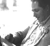 Black and white photo of Jim in profile reading a book with a bemused smile on his face and a white carnation on his white jacket