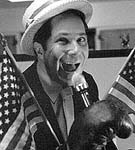 Black and white photo of Jim in same straw hat, white jacket replaced with a black jacket, now holding a microphone with his hand inside a boxing glove, two American flags crossing his chest, his mouth open wide and a wild look in his eye, light from below casts mysterious shadows on his face to add to his caveman-as-politician image
